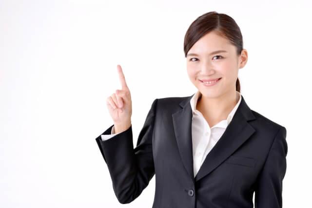 人差し指を立てるスーツ姿の女性